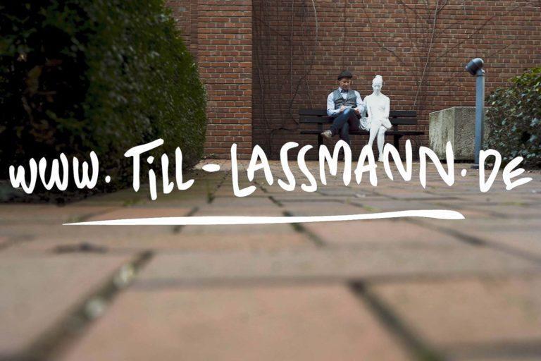 Eventzeicher Till Lassmann sitzt auf einer Parkbank neben einer Frauen Statue