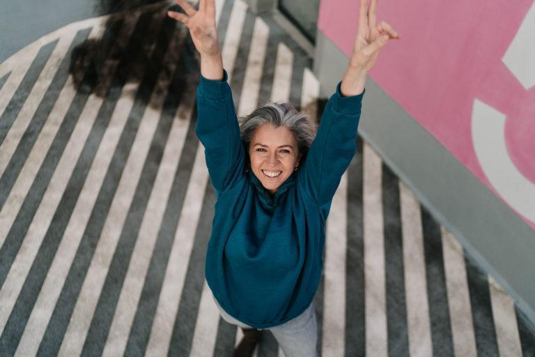 Frau streckt glücklich die Arme mit victory Zeichen in den Hilmmel