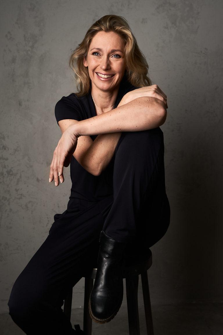 Schauspielerin Tokessa Martinius sitzt auf einem Hocker und lächelt