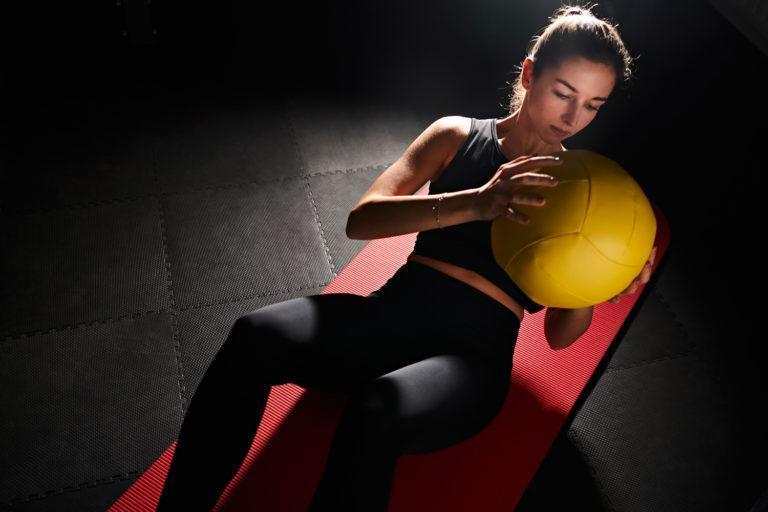 Frau macht Sport mit Ball auf einer rote matte